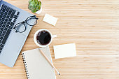 flat lay composition with notebook, pen, coffee, plant, laptop on wood background. top view