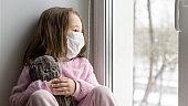 COVID-19 coronavirus concept, sad kid in medical mask looks out window