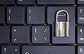 Small locked steel padlock on a black laptop keyboard