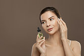 Young beautiful woman spa model with cosmetic oil. Facial treatment, body care and alternative medicine concept