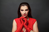 Stylish woman brunette with makeup and dark hair wearing red dress and red silk gloves on black background