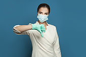 Woman doctor in protective medical mask showing thumb down on blue background