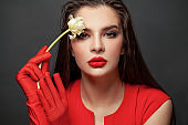 Fashion model in red dress portrait. Elegant woman with red lips makeup on black background