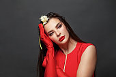 Young beautiful woman in red dress. Female model with red lips makeup