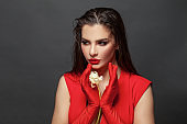 Valentine's Day. Loving woman. Beautiful female model in a red dress on black. Red lipstick makeup on the lips from the beautiful lady.