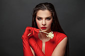 Portrait of a beautiful young woman brunette in red dress on black