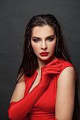 Sensual beautiful brunette woman posing in red dress.