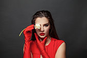 Gorgeous elegant brunette woman wearing fashion red dress and silk gloves on black background