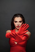Stop gesture. Brunette woman hands in red silky gloves showing stop gesture, negation, denial and no