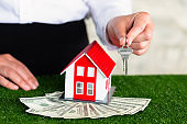 Real Estate Agents Deliver Key Rings and Red Houses to Place on Banknotes Real estate concept, mortgage, home agent, contract to buy a house, sell or rent Home trading.