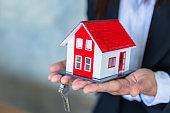 The keys and the red house are in the hands of real estate agents, real estate sales ideas, rental housing, buying apartments, selling apartments.