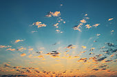 Beautiful sunrise with sun rays and clouds in the blue sky.