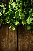 Hanging Bunches of Drying Aromatic Herbs and Spices. Wooden Background. Copy Space.