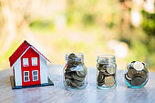 Red roof house model. Coins that are stacked from low to high. Financial and banking concepts Preparing for home purchase and real estate economic growth. Home mortgage finance.