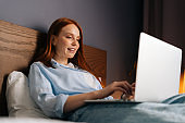 Close-up of relaxed redhead young woman looking on laptop screen while lying on bed.