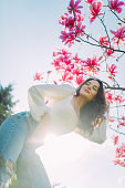 Woman poses near blooming magnolia tree against sky background.