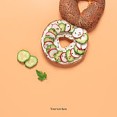 Fresh bagel with cream cheese, radish and cucumber on a pastel peach background. Creative layout. Top view, flat lay.