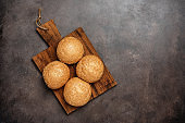Fresh homemade sesame buns for a hamburger on a dark rustic background. Top view, flat lay, copy space.