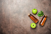 Apple juice in a bottle, green apple and fresh mint leaves on a dark rustic background. Top view, flat lay, copy space.