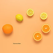 Oranges and lemons on a pastel yellow background. Creative layout. Top view.
