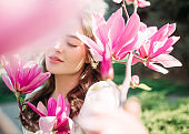 Portrait of woman in garden among blooming magnolia.