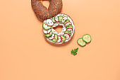 Fresh bagel sandwich with cream cheese and spring vegetables on a pastel peach background. Top view, flat lay.