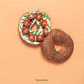 Fresh bagel sandwich with cream cheese, cherry tomato and arugula. Pastel peach background. Top view, flat lay. Creative layout.
