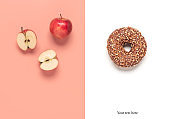 Apple and donut. Creative layout. Food choice concept. Double white-pink background. Top view, flat lay.