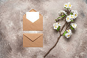 Blank wedding card mockup in brown envelopes and cherry blossom branch artificial . Beige grunge background. Spring stationery scene. Top view, flat lay.