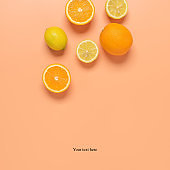 Fresh orange and lemon on a pastel peach background. Top view, flat lay. Summer tropical background. Creative layout.