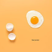 Fried egg and shells on a pastel yellow background. Creative layout. Minimalistic still life. Breakfast concept. Top view, flat lay, place for text.