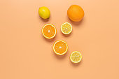 Halves of oranges and lemons on a pastel yellow background. Creative layout. Top view.