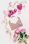 Valentine's Day composition. Blank greeting card mockup in envelope, rose, macaroon, gold ribbon, heart and rose petals. White painted wood background. Template for your design. Top view, flat lay.