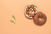 Fresh bagel sandwich with cream cheese, cherry tomato and arugula. Pastel peach background. Top view, flat lay.