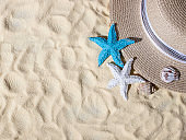 Seashells, a straw hat on the sand with space for text. Beautiful summer beach vacation.