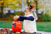Little toddler girl dressed as a witch trick or treating on Halloween. Happy child outdoors, with orange funny hat and pumpkin bag for sweet haunt. Family festival season in october. Outdoor activity