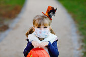 Little toddler girl dressed as a witch with medical mask on face trick or treating on Halloween. Child outdoors, with funny hat and bag for sweet haunt. Pandemic corona virus quarantine lockdown time