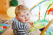 Portrait of little child, cute adorable baby boy playing with colorful toys. Happy, curious kid at home, indoors.