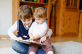 School kid boy reading book for little toddler baby girl, Two siblings sitting together and read books. Beautiful lovely family in love, cute baby and child having fun at home, indoors.