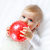 Cute baby playing with red gum ball, crawling, grabbing