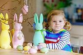 Cute little toddler girl decorating tree and bunny with colored pastel plastic eggs. Happy baby child having fun with Easter decorations. Adorable healthy smiling kid in enjoying family holiday