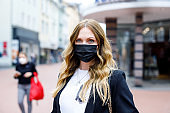 Portrait of young beautiful woman wearing medical mask as protection against corona virus. Covid pandemic time in Europe and in the world. Safety for people. Woman in summer city.
