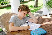 Hard-working sad school kid boy making homework during quarantine time from corona pandemic disease. Upset tired child on home schooling in coronavirus covid time, schools closed.