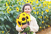 Cute adorable school girl on sunflower field with yellow flowers. Beautiful preschool child with blond hairs. Happy healthy little daughter, smiling and holding bouquet
