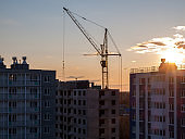 high-rise crane in the construction of high-rise buildings in the city district, against the background