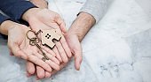 Closeup real estate or couple hands holding and giving key house with copy space isolated on marble background. Hands of man and woman buy new house. Together love startup new family concept banner