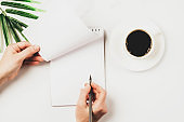 Woman writes makes notes by hand in blank notebook, a cup of coffee the desktop