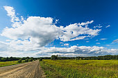 Summer countryside nature landscape. Blue sky white clouds green meadows rural road. Horizontal frame