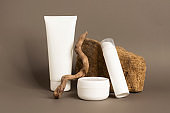 A group of cosmetics in various bottles modern abstract podium natural materials
