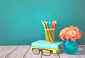 Teacher's day. Knowledge day concept. Stack of books,pencils,glasses and flowers vase.